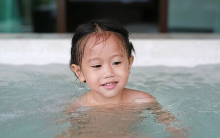 Little girl playing water in the bathtub.