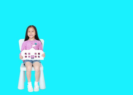 Happy little Asian child girl holding mock-up paper school sitting on kid chair isolated over Cyan background with copy space. Education and back to school concept.