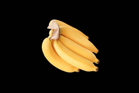 Bunch of ripe bananas isolated over black background. Standard-Bild
