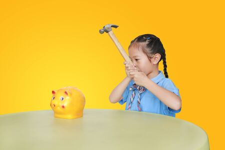 Little child girl in school uniform taking hammer trying to broke piggy bank isolated on yellow background at table. Schoolgirl with Money saving concept.