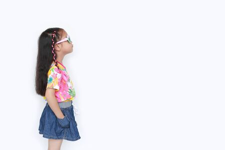 Beautiful little Asian kid girl wearing a flowers summer dress and sunglasses isolated on white background with copy space. Summer and fashion concept. Side view. 写真素材
