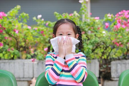 Little girl sneezing on nose with tissue paper while outdoor. Standard-Bild