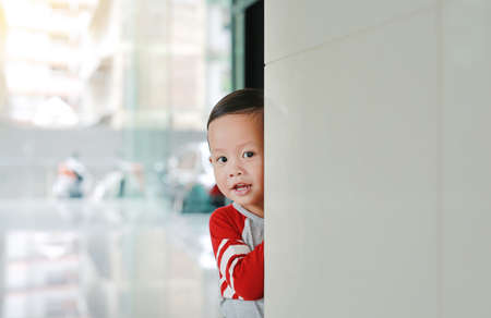 Happy little Asian baby boy hide behind a corner room. Small children playing peekaboo game indoor. 版權商用圖片