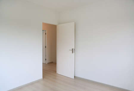 Open door in the white room of new house