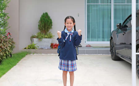 Confident asian little kid girl in kindergarten school uniform raise hands up expression before leave home to go to school at morning