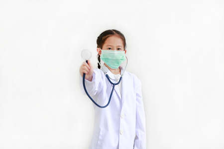 Asian child girl showing stethoscope while wearing doctor's uniform and medical mask isolated on white background. Focus at kid face. Foto de archivo