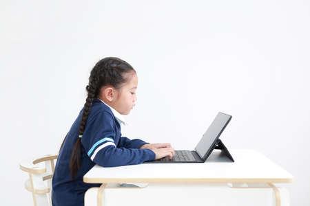 Asian little kid girl in school uniform using laptop on table isolated on white background, Studio shot
