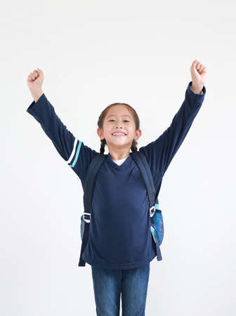 Happy asian little child girl in school uniform with backpack raise hands up isolated on white background. Studio shot.