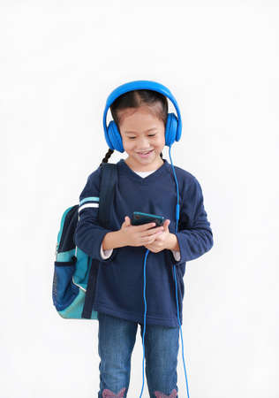 Portrait happy asian little kid girl enjoy with smartphone and headphones isolated on white background Foto de archivo
