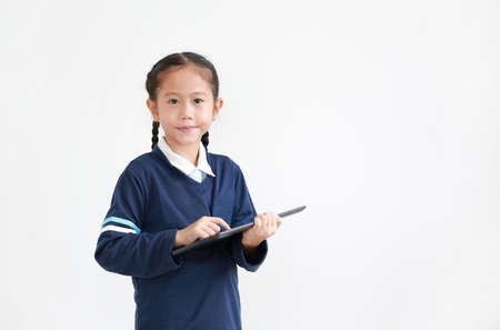 Portrait of asian little kid girl in casual school uniform using tablet isolated on white background with looking camera. Studio shot