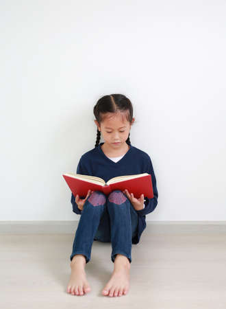 Asian little girl in school uniform reading a book and sitting against white wall in the room.