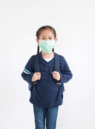 Portrait asian little kid girl in casual school uniform wearing medical mask with backpack isolated on white background. Studio shot