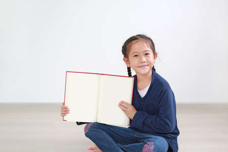 Caucasian kid sitting in room and holding blank page of book. Portrait asian little kid girl open book. Foto de archivo