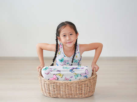 Portrait of smiling asian little child girl sitting in rattan picnic basket in room at home