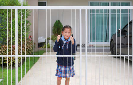 Portrait smiling asian little girl in kindergarten uniform at door fence of house before go to school at morning.