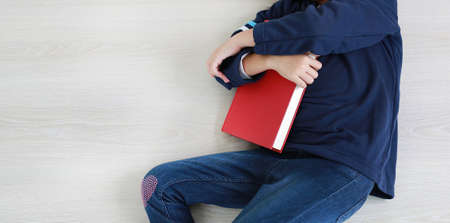 Close up body of child in casual school uniform with hugging book lying on wood laminate flooring. Education concept