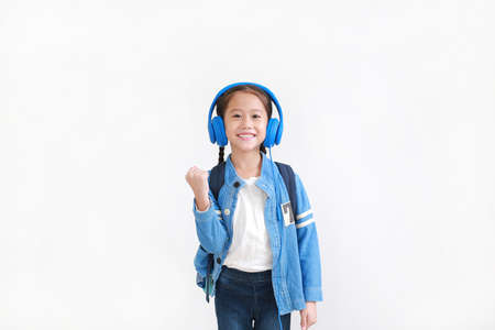 Happy asian little kid girl raise hand up enjoy with headphones isolated on white background. Foto de archivo