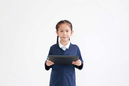 Portrait of asian little child girl in school uniform using tablet isolated on white background with looking at camera
