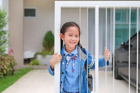 Happy asian little girl in kindergarten uniform at door fence of house before go to school at morning.