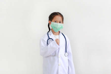 Portrait little asian kid girl with stethoscope while wearing doctor's uniform and medical mask isolated over white background