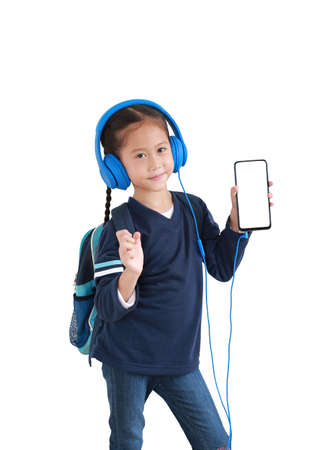 Portrait happy asian little kid girl enjoy with smartphone and headphones isolated on white background. Child showing blank white screen on mobile phone. Foto de archivo