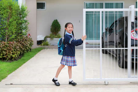 Portrait of happy asian little kid girl in school uniform trying push and pull door fence of house to close or open before leave home to go to school at morning.