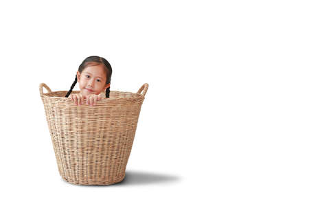 Smiling asian little kid girl sitting in rattan basket isolated over white background with copy space Foto de archivo