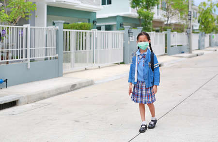 Asian little child girl in kindergarten uniform and wearing medical mask walking on street leave home to go to school at morning