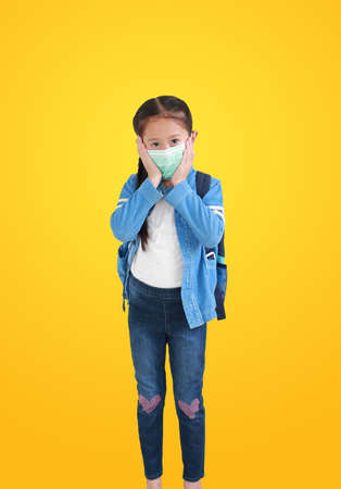 Asian child girl wearing medical mask isolated on yellow background