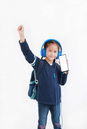 Confident asian little kid girl raise hand up enjoy with smartphone and headphones isolated on white background. Child showing blank white screen on mobile phone Foto de archivo