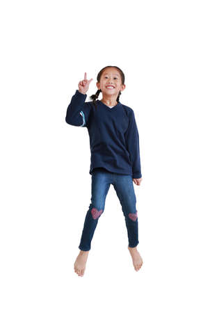Smiling asian child girl jumping on air with showing two finger gesture as sign as fighting isolated on white background