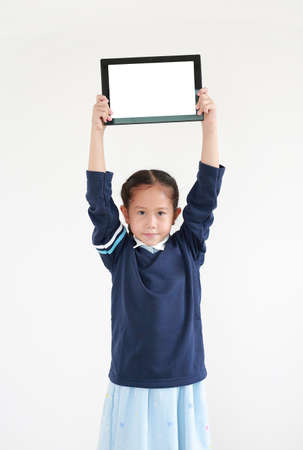 Portrait asian little child girl in school uniform raise up tablet over head showing blank screen isolated on white background with looking at camera Foto de archivo