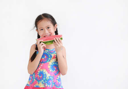 Smiling asian little kid girl eating watermelon isolated on white background