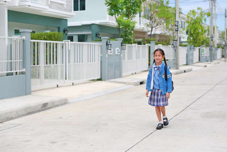 Cheerful asian little child girl in kindergarten uniform walking on street leave home to go to school at morning