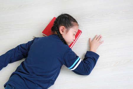Portrait asian little child girl sleeping on a book on wood laminate flooring. Education concept Foto de archivo