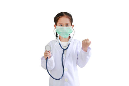 Portrait asian little kid girl showing stethoscope and hand fight while wearing doctor's uniform and medical mask isolated on white background.
