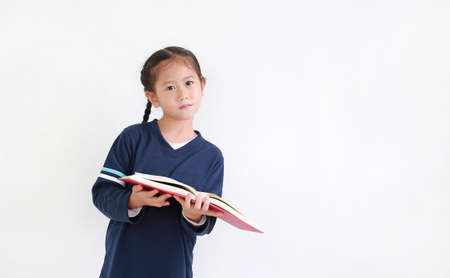Portrait asian little girl in casual school uniform holding open book with looking camera isolated on white background with copy space.