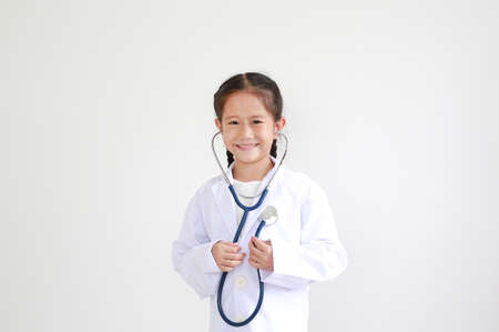 Smiling asian little child girl in doctor uniform with stethoscope isolated on white backgorund Foto de archivo