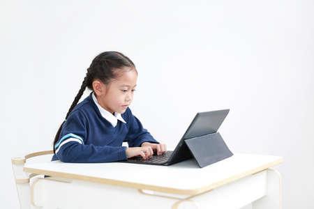 Portrait asian little child girl in school uniform using laptop on table isolated on white background, Studio shot Foto de archivo