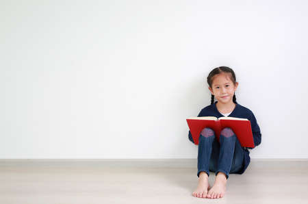 Portrait asian little kid girl in school uniform reading a book and sitting against white wall in the room with copy space.