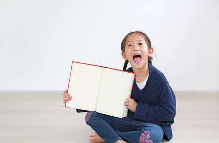 Asian little child girl laughing with open book show blank page. Kid sitting in the room and holding a book.