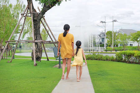 Rear of mother and daughter hand in hand relax walking in garden outdoors. Mum and child spending time together in summer park Standard-Bild
