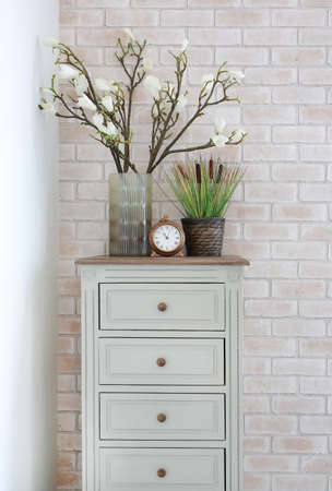 Artificial flower and green grass in vase with clock on the table in modern living room. Interior design brick wall background Archivio Fotografico