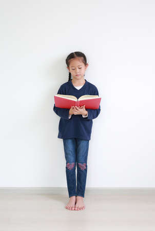 Portrait asian little child girl in casual school uniform reading a book and standing against white wall in the room Stock Photo