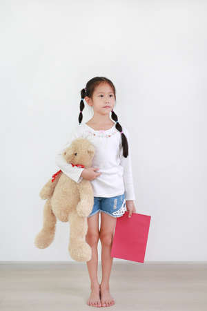 Asian asian little child girl carrying a teddy bear doll and book indoor with looking out.