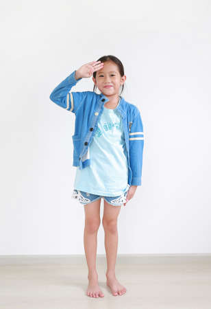 Portrait of asian little child girl saluting with hand at forehead indoor. Full-length.