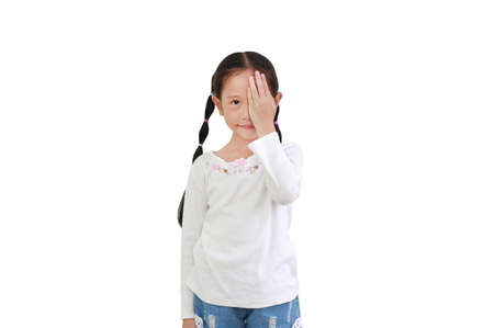 Portrait of little asian child girl closing one eye with hand isolated on white background looking camera. Kid as vision test.