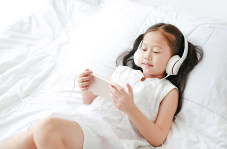 Happy little Asian girl using headphones listen music by smartphone smiling while lying on bed at home. Stock Photo