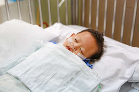 Baby boy age about 1 year old sleeping on patient bed with getting oxygen via nasal prongs to assure oxygen saturation. Intensive care at hospital. Respiratory support. 版權商用圖片
