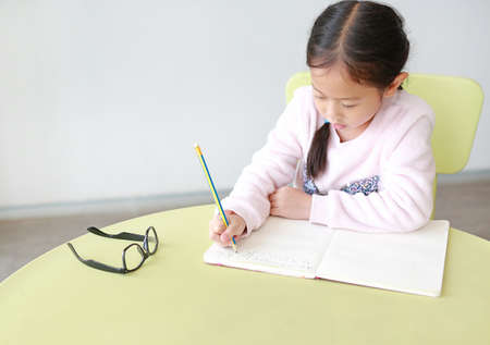 Portraits of little Asian girl writes in a book or notebook with pencil sitting on kid chair and table in classroom.